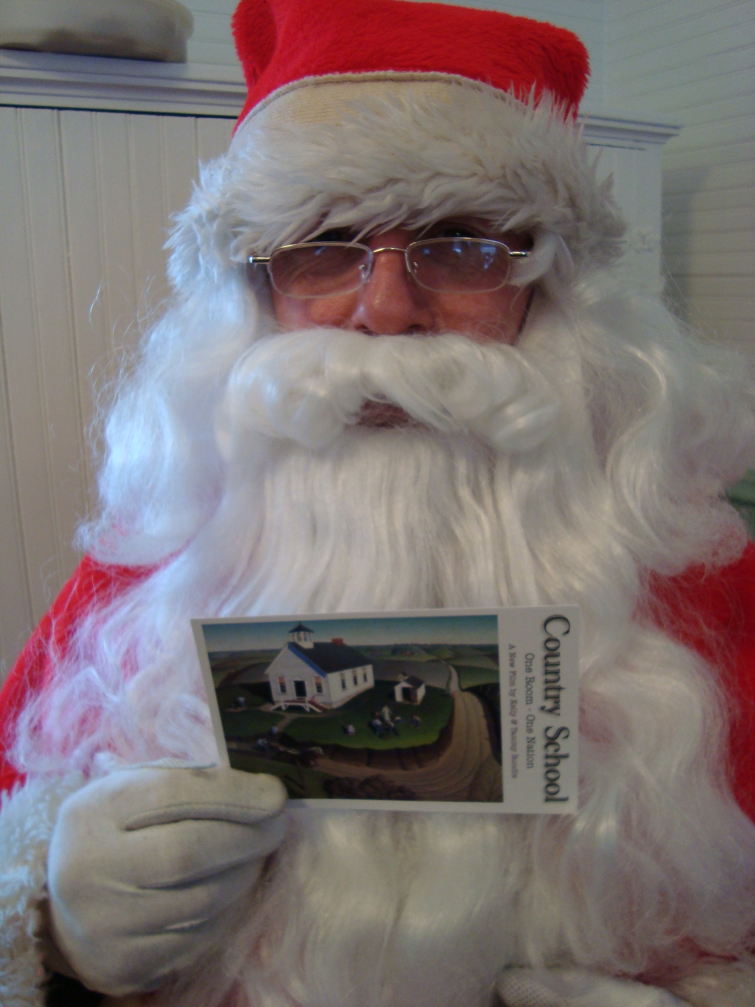"Santa Claus holds a ""Country School: One Room - One Nation"" postcard."
